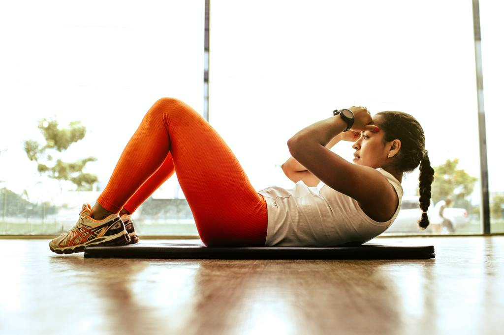 Image of woman doing sit-ups. Exercise can increase productivity
